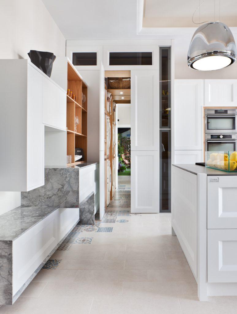 Cocina blanca con un pequeño cuarto de lavado realizada por Steven ...
